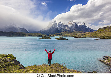 girl in red jacket with hands up standing above lake in...