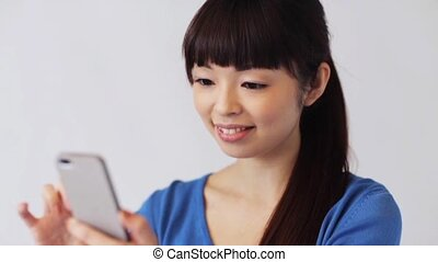 happy smiling asian woman with smartphone - people,...