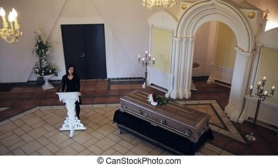 sad woman and coffin at funeral in orthodox church