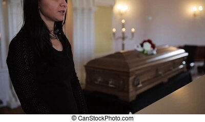 woman with wipe and coffin at funeral in church - funeral,...