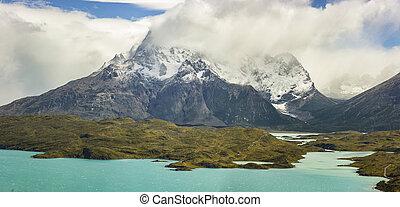 mountains of patagonia in haze at sunrise near blue lake