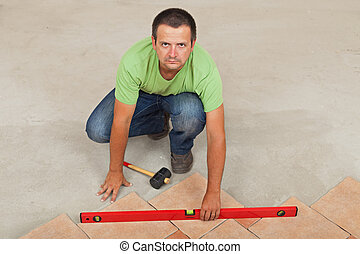 Man laying ceramic floor tiles - checking with a level, top view