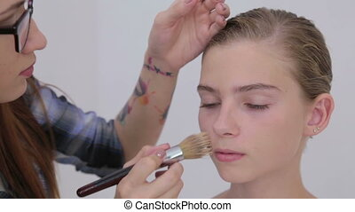 5 shots. Makeup artist applying liquid tonal foundation on...