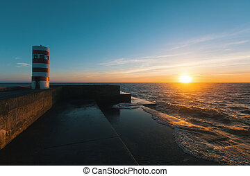 Beautiful sunset on an ocean pier with a lighthouse.