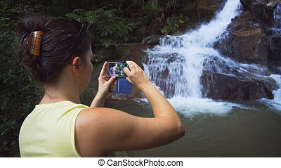 Tourist Recording Video of Natural Waterfall using Samsung...