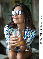Girl with cocktail - Lovely smiling girl in sunglasses sits...