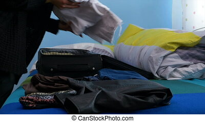 Hands of woman packing up her luggage in a hurry