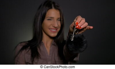 Attractive woman holding new house key in her hand and...