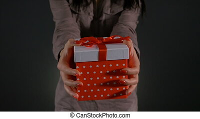Teen woman showing gift box to the camera