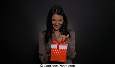 Woman opening her present expecting a pleasant surprise and getting an unpleasant one