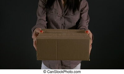 Woman hands holding and showing a cardboard box package in...