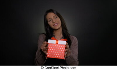 Young beautiful girl smiling and offering a gift box