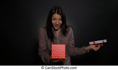 Excited and surprised young woman opens her present gift box on her birthday