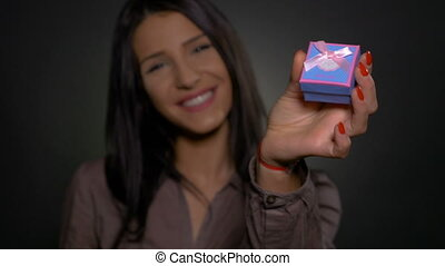 Happy woman showing to the camera a small proposal gift box
