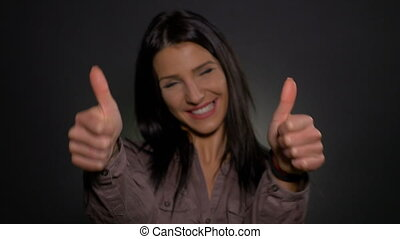 Business woman making thumbs up gesture
