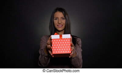 Happy beautiful woman holding and showing a birthday gift...