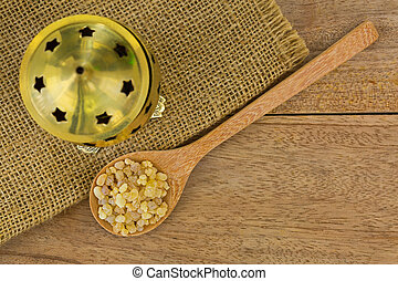 Spoon of aromatic yellow resin gum next to brass incense...