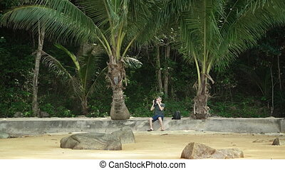 Lone Tourist Sits on the Beach taking Photos. - Lone tourist...