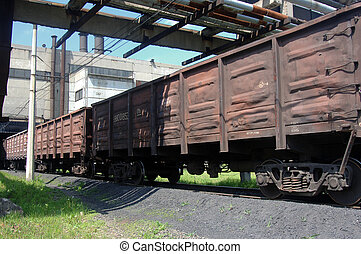 freight train traveling on the background of the plant