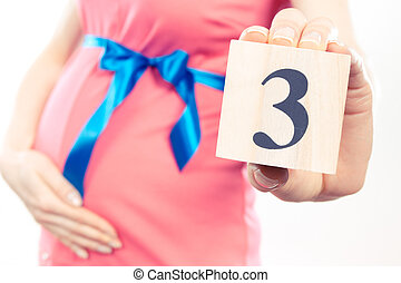 Vintage photo, Hand of woman showing number of third month of pregnancy, expecting for newborn concept
