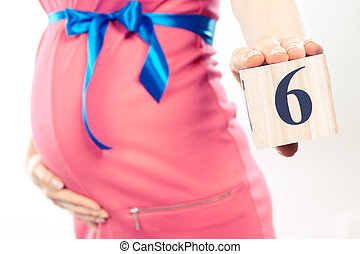 Vintage photo, Hand of woman showing number of sixth month of pregnancy, expecting for newborn concept