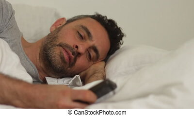 young man in bed with phone - Shot of young man in bed with...