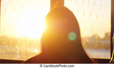 Woman looking standing near the window with view on sunset in city and lense flare effects