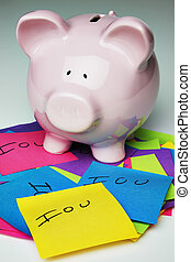 Piggy bank with IOU - Piggy bank placed on pile of IOUs with...