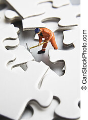 figurines with with puzzle pieces - Worker figurines placed...