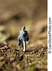 figurines in the dirt - Business figurines placed outside in...