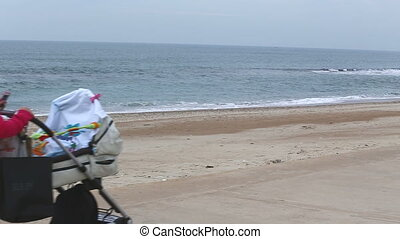 woman with stroller fast walking by the ocean