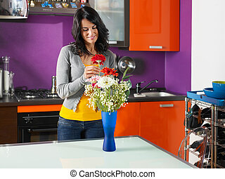 woman arranging flowers in pot - mid adult woman putting...