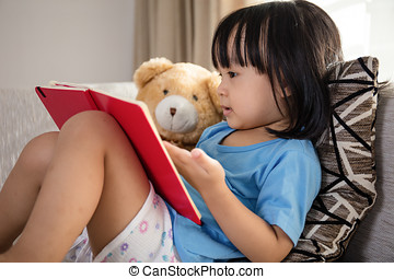 Asian Chinese little girl reading book with teddy bear on...