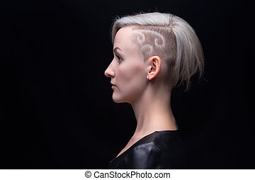 Portrait of blond woman with shaved head on black background