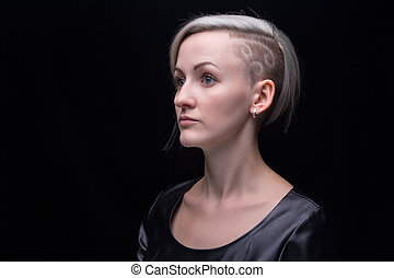 Blond woman with shaved head on black background
