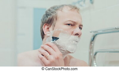 a man shaves in the bathroom. Slow motion