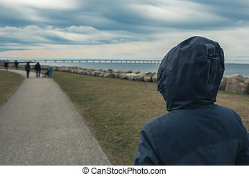 Lonely hooded female person from behind standing at seashore...