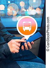 Woman using mobile phone app to purchase bus electronic ticket