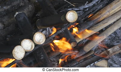 Cooking sugarcane on charcoal - Preparation of sugar cane at...