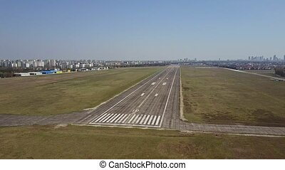 Aerial shot of a city airport plated runway and taxiing...