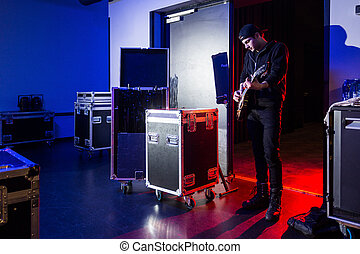 Roadie playing guitar backstage, standing near the stage...