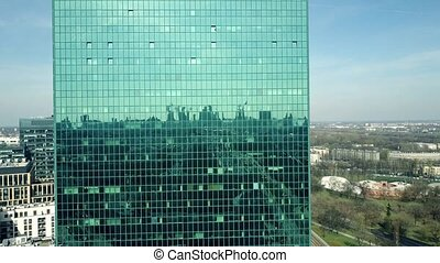 Aerial shot of a modern office building facade reflecting cityscape on a sunny day. 4K clip