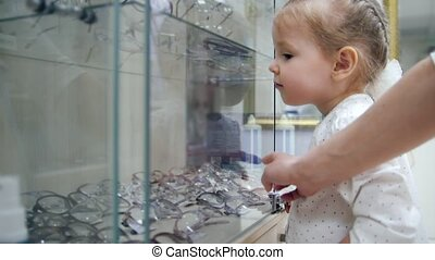 Little girl in store chooses glasses. Child put the Finger at Something and Mom Allows to Buy It