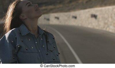 Long hair brunette girl walking on the road