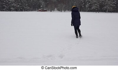 woman walking in snow forming heart shape footprints in winter. 4K
