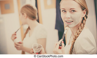 Woman applying with brush clay mud mask to her face -...