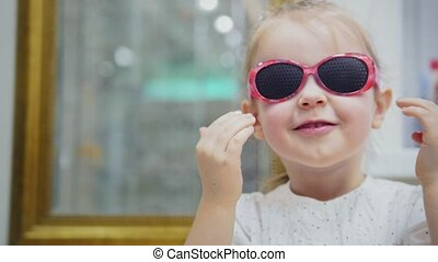 Little girl tries fashion medical glasses near mirror - shopping in ophthalmology clinic