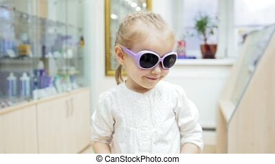 Little Girl tries medical blue glasses - shopping in clinic...
