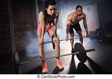 Fit couple performing deadlift exercises
