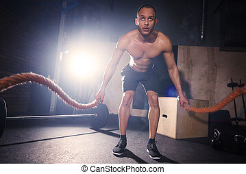 Male athlete working with rope at gym